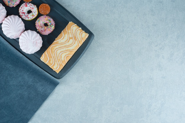 Рулет из торта, печенье, пончики и мармелад на темно-синей доске на мраморе.
