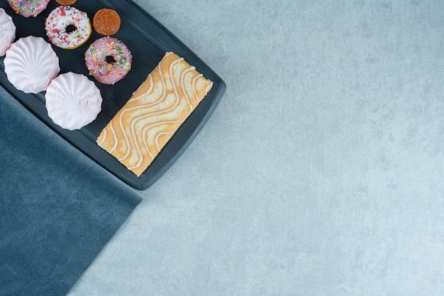 Rotolo di torta, biscotti, ciambelle e marmellate su un bordo della marina su marmo.