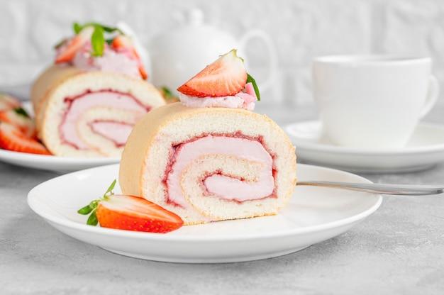 灰色の背景の白いプレートに新鮮なイチゴ、ジャム、クリームチーズとケーキロール。スペースをコピーします。