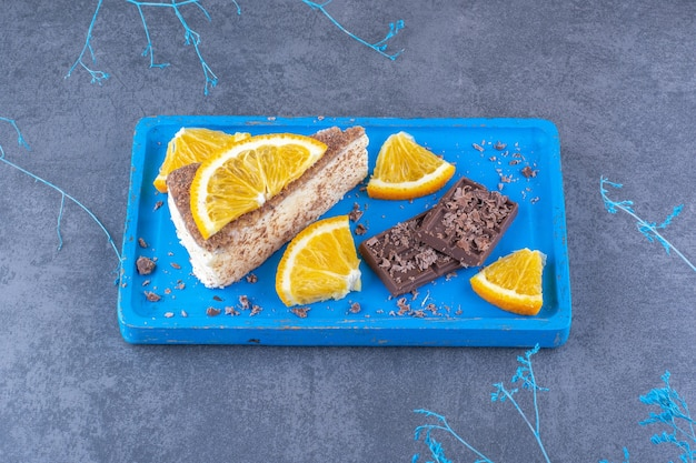 Cake slice adorned with chopped orange slices, on a blue platter with chocolate bits on marble surface