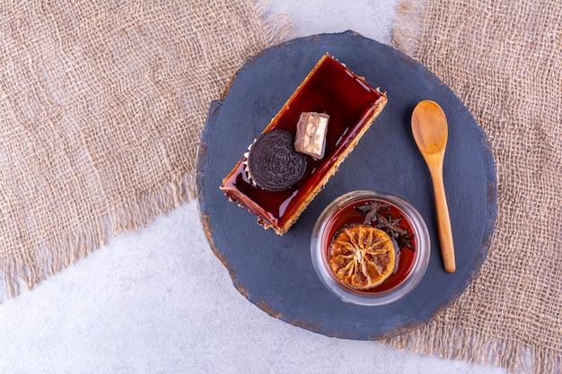 케이크 조각, 차 유리 및 어두운 보드에 숟가락. 고품질 사진