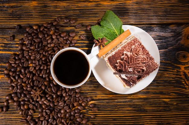 Кусочек торта в тарелке с кофе и зернами