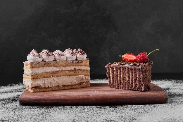 Кусочек торта на деревянном блюде.