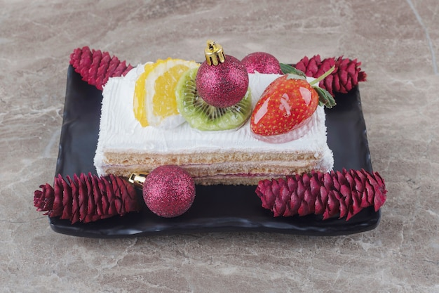 Cake slice on a platter adorned with festive decorations on marble