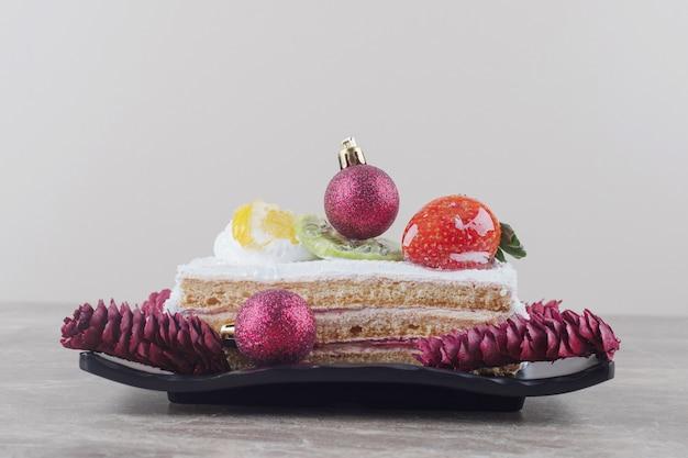 Fetta di torta su un piatto decorato con decorazioni festive su marmo