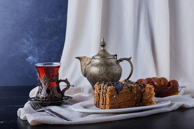 Fetta di torta in un piatto bianco con sciroppo di cioccolato e tè.