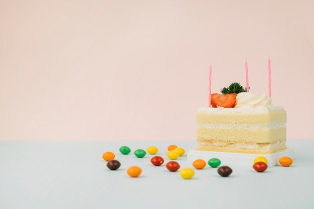Cake slice with candles and candies on table against pink background