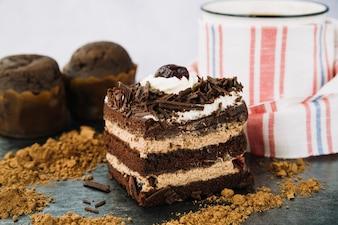 Cake slice with cocoa powder and coffee mug