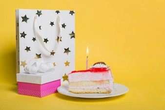 Cake slice with lighted candle; star shape shopping bag; and gift box on yellow background