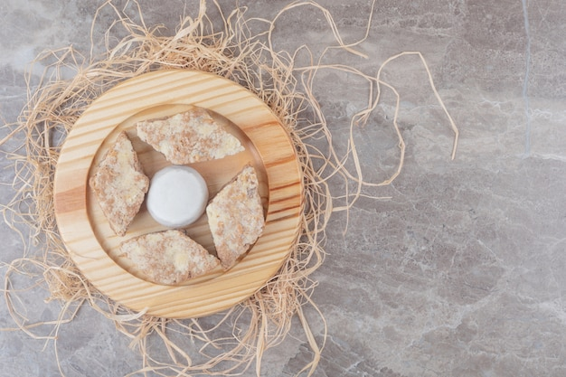 大理石の木製プレート上のバニラパウダーコーティングされたクッキーの周りのケーキスライス