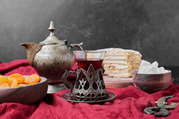 Fette di torta e confettura su asciugamano rosso con tè.