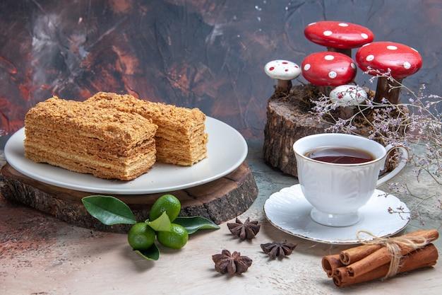 Кусочки торта медовый торт с чашкой чая на сером