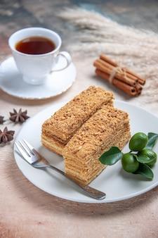 Fette di torta torta al miele con una tazza di tè su grigio