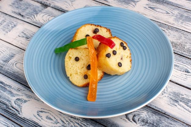 Ломтики торта внутри синей тарелки с шоколадными чипсами и мармеладом на деревенском сером столе