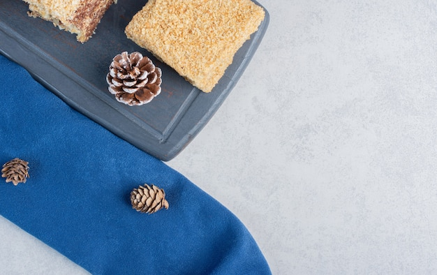 대리석 표면에 소나무 콘과 함께 해군 보드에 케이크 조각