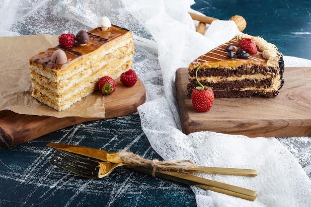 周りにベリーと木の板のケーキのスライス。