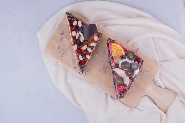 Fette di torta a forma di triangolo con cioccolato, noci e frutta su un piatto di legno