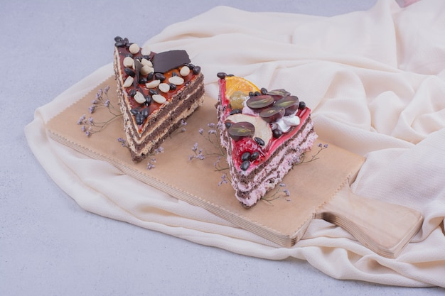 Cake slices with caramel, chocolate and nuts on wooden platter.
