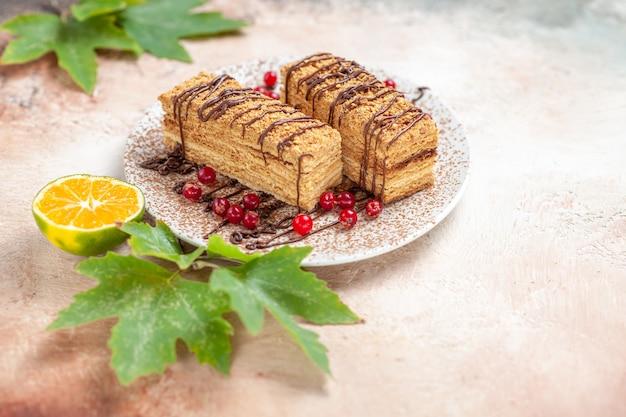 Fette di torta con glassa al cioccolato e bacche rosse su grigio