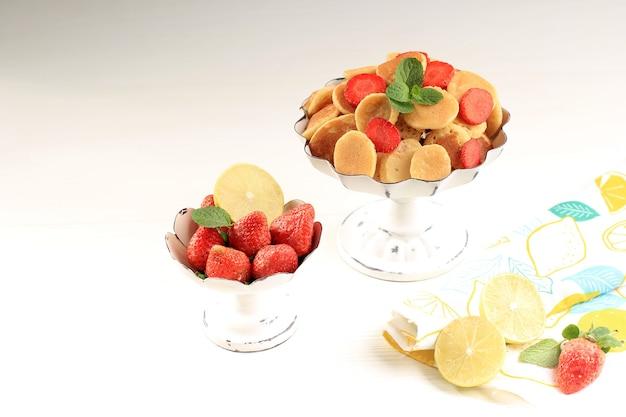 白い背景にミントの葉とレモンスライスを添えて、小さなパンケーキシリアルとイチゴのケーキスタンド。トレンディな料理。ミニシリアルパンケーキ。コピースペース付き水平