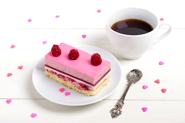 Cake strawberry mousse, coffee americano, sweets hearts on white wooden background