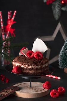 ラズベリーと新年の休日の装飾で3つのチョコレートをケーキ