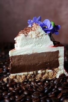 Торт тирамису в шоколадной глазури с кремом маскарпоне, украшенный кофейными зернами и фиалками