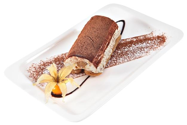 Торт тирамису на прямоугольной керамической тарелке, украшенной ягодами физалиса, изолированными на белом фоне.