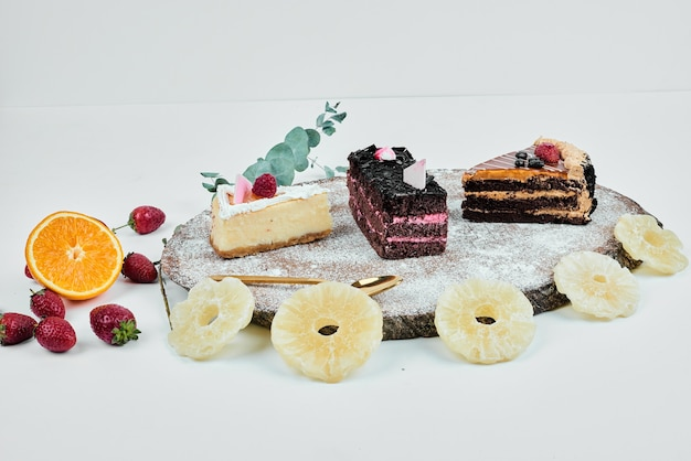 Cake varieties on a wooden platter with dry fruits.