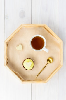 Торт с чашкой чая на подносе на деревянном столе
