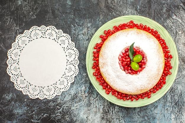 ベリーのケーキレースのドイリーの横にザクロとライムのケーキ