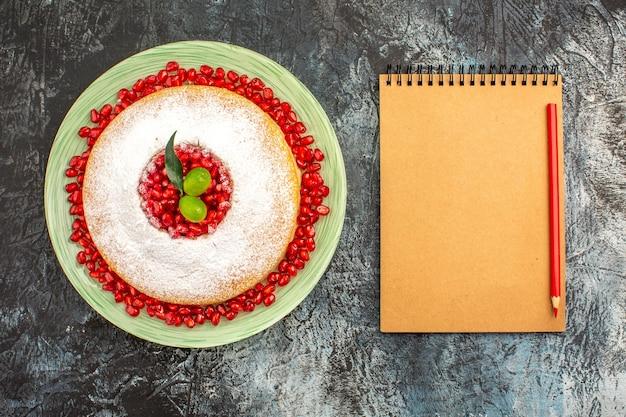 ノートの鉛筆の横にあるベリーとザクロとライムのケーキ