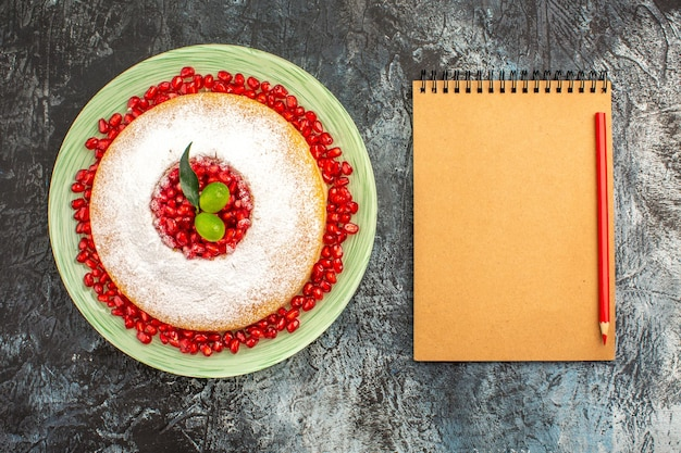 Torta ai frutti di bosco una torta al melograno e lime accanto al taccuino matita