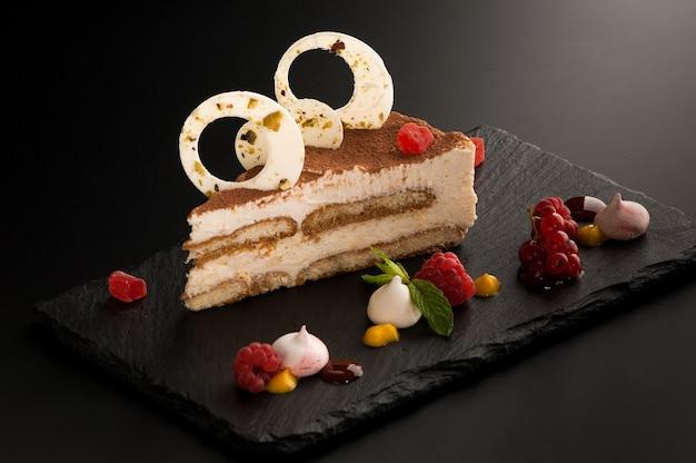 多くの装飾的な石の暗い背景にベリーとケーキ