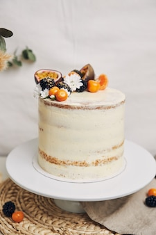 Cake with berries and passionfruits next to a plant