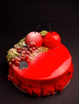 Cake with berry mousse in the mirror red glaze decorated with a molecular biscuit. on the black background