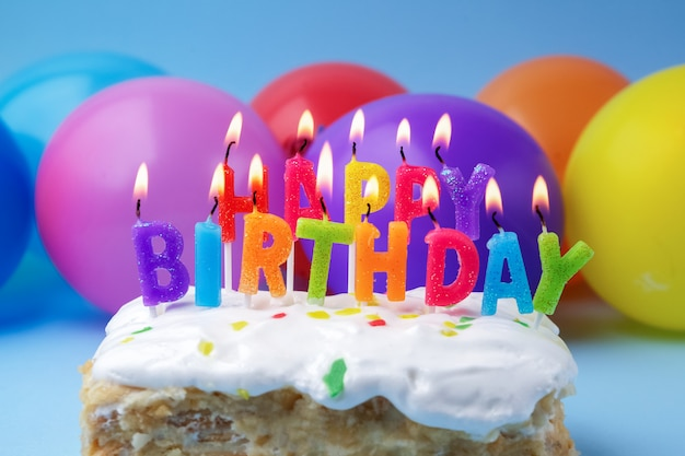 Cake with birthday greetings from burning candles on a colored background