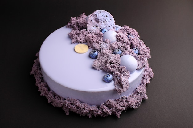 Cake with blackberry mousse in the mirror glaze decorated with a molecular biscuit. on the black background.