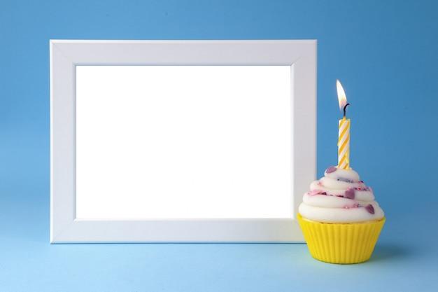 青色の背景のクローズアップのキャンドルとフォトフレームとケーキ