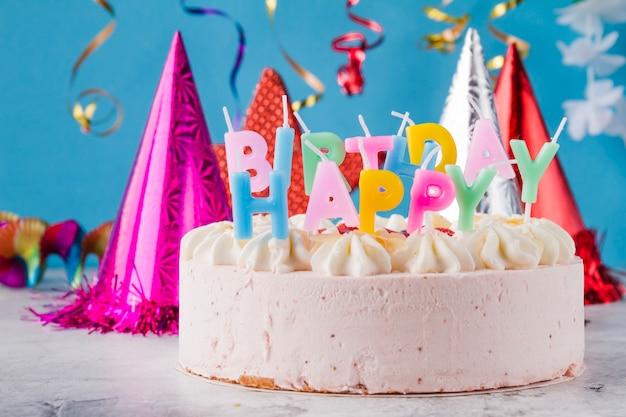 Torta con candele e cappelli di compleanno