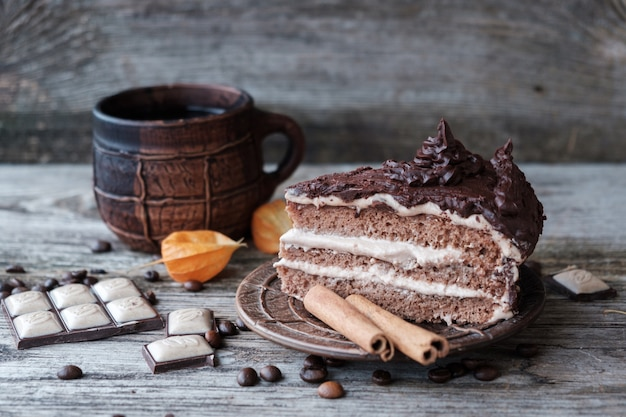 Cake with chocolate cream and a ceramic coffee mug on wooden boards