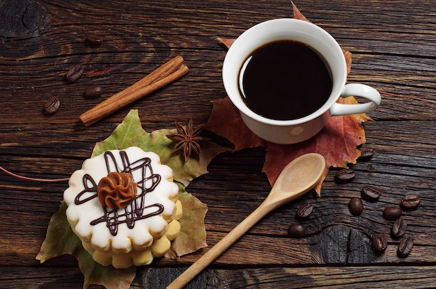 Cake with chocolate cream, cup of coffee and autumn leaves on old wooden background