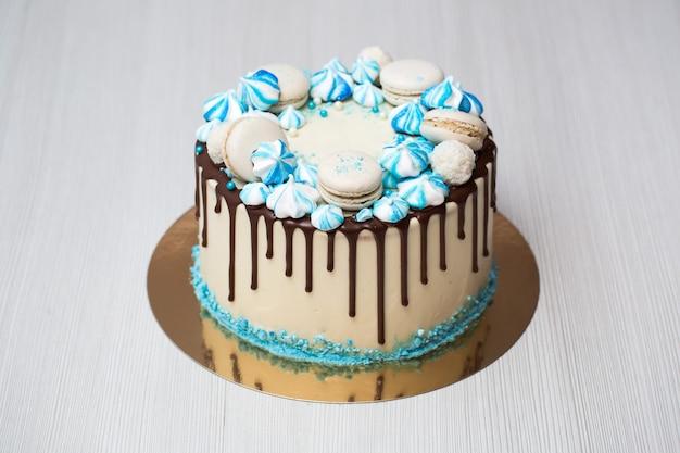 Cake with chocolate streaks, blue meringue and macaroons