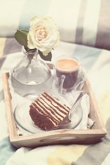 Торт с кофе и цветком в подносе на кровати