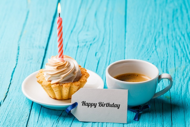 Cake with cream and a candle, with a cup of coffee and a blank card on a blue table