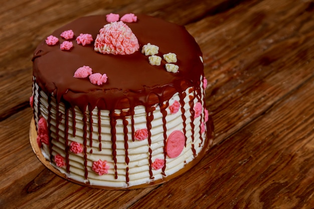 Cake with cream and chocolate with roses on the old board