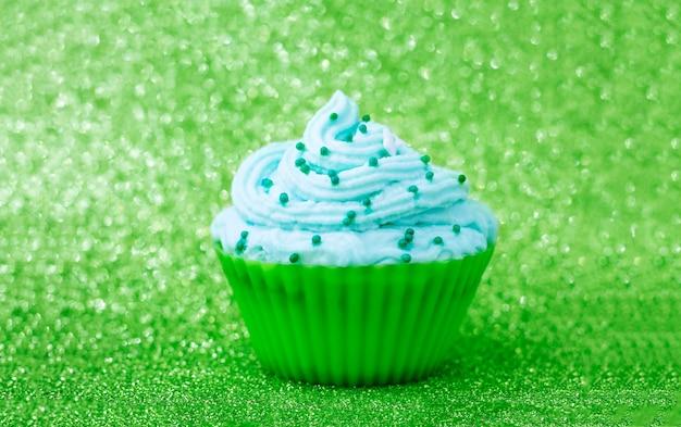 Bokeh와 녹색 배경에 크림 케이크. 휴일 카드 개념입니다. 선택적 초점.