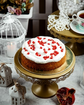 Cake with cream and pomegranate on top
