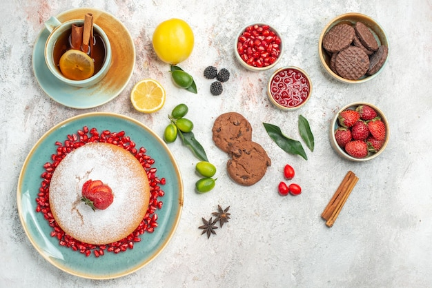 Cake with a cup of tea a cup of black tea with cinnamon sticks cake of strawberries star anise chocolate cookies on the table