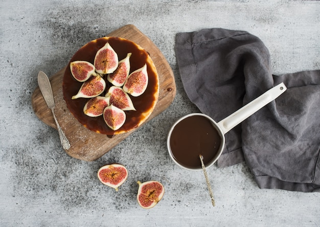 Cake with fresh figs and salted caramel on wooden serving board over grunge table